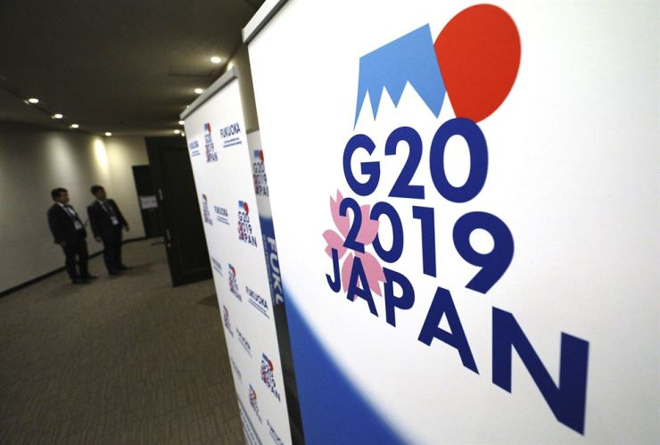 Staff stand near the emblem of G20 2019 Japan at the entrance of the press center of G20 Finance Ministers' and Central Bank Governors' Meeting in Fukuoka, western Japan, Friday. AP-Yonhap