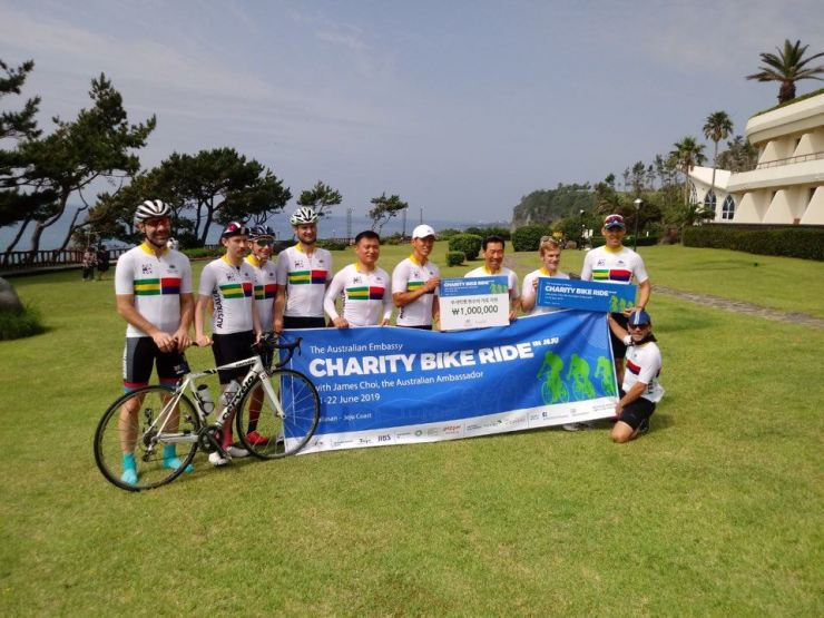 Australian Ambassador to Korea James Choi, fourth from right, poses with hip-hop duo Jinusean member Sean, fifth from right, and other participants on a charity bike ride led by Choi on Jeju Island, June 21. / Embassy of Australia