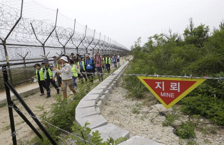 In this June 14 file photo, hikers and journalists walk along the DMZ Peace Trail in the demilitarized zone in Goseong, South Korea. Eyeing a history-making photo opportunity, U.S. President Donald Trump has issued a Twitter invitation to North Korean leader Kim Jong-un to join him for a hand shake during a visit by Trump to the demilitarized zone. AP