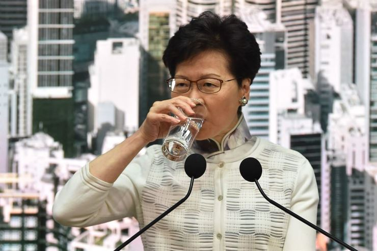 Hong Kong Chief Executive Carrie Lam takes a drink of water as she speaks during a press conference at government headquarters in Hong Kong on June 15. AFP-Yonhap