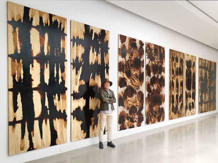 Artist Ci Kim poses in front of his coffee stain works on display at his 10th solo exhibition 'Voice of Harmony' at Arario Gallery Cheonan in Cheonan, South Chungcheong Province. Courtesy of Arario Gallery