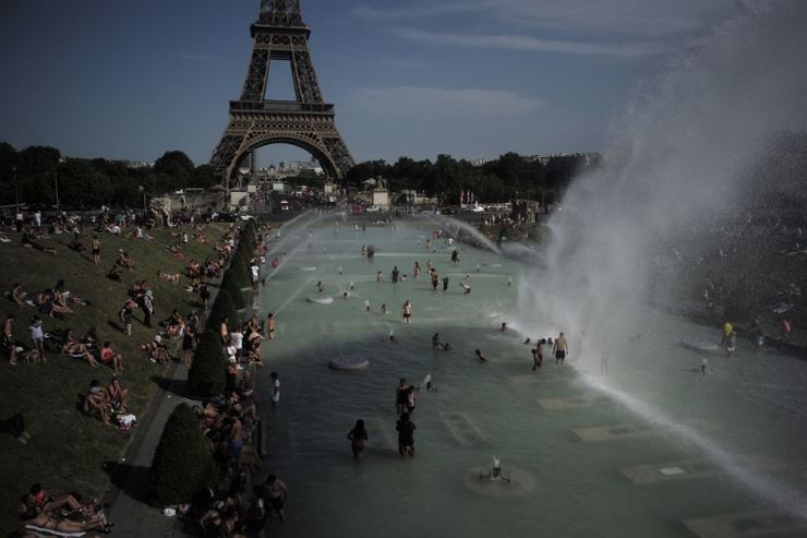 People cool off in the fountains of the Trocadero Gardens, in front of the Eiffel Tower, in Paris, June 28. Schools are spraying kids with water and nursing homes are equipping the elderly with hydration sensors as France and other nations battle a record-setting heat wave baking much of Europe. AP