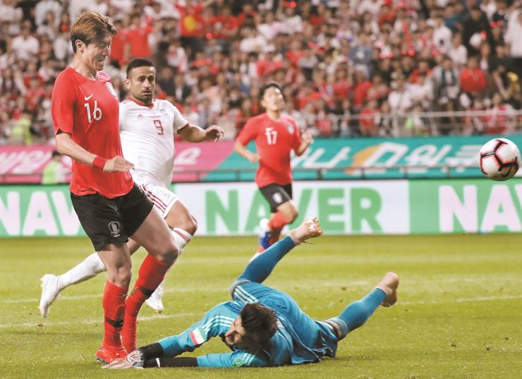 Korea's Hwang Ui-jo kicks the ball over Iran's goalkeeper to score the first goal in a friendly match at the Seoul World Cup Stadium, Tuesday. The game ended in a 1-1 tie. Yonhap