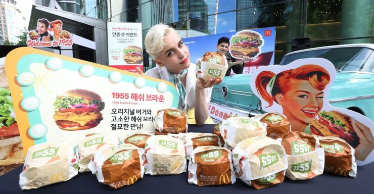A model promotes McDonald's Korea's 1955 Hash Brown burger at the burger chain's headquarters in Jongno-gu, Seoul, Tuesday. The limited edition burger is the original 1955 Burger with an added hash brown, released to commemorate the brand's original burger served at McDonald's first outlet in the U.S. in 1955. It will be available until July 16. Yonhap
