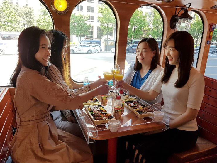 Passengers enjoy a lunch box meal on the bus. 서울시티투어버스 승객들이 도시락을 먹고 있다. /Courtesy of Seoul City Tour Bus
