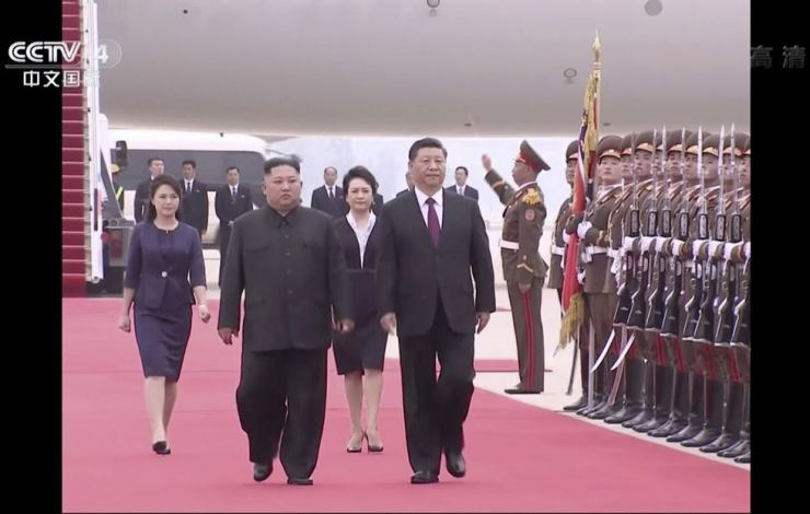 In this image taken from a video footage run by China's CCTV, North Korean leader Kim Jong-un, left, and Chinese President Xi Jinping, right, walk together on Xi's arrival at an airport in Pyongyang, Thursday afternoon. CCTV via AP