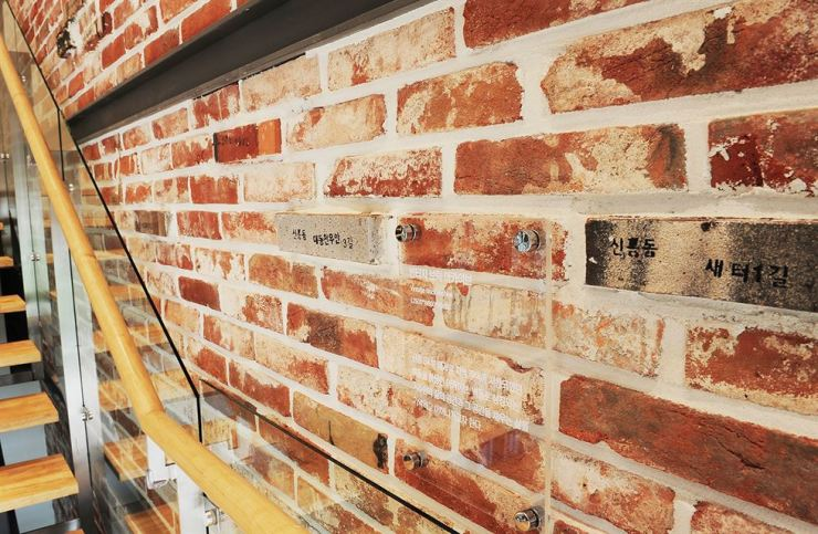A wall of a staircase at building showcasing a model home for the SK View apartment complex in Shinheung-dong, Daejeon. The sidewall used repurposed bricks collected from demolished buildings at the site for the new apartment complex. Courtesy of SK E&C
