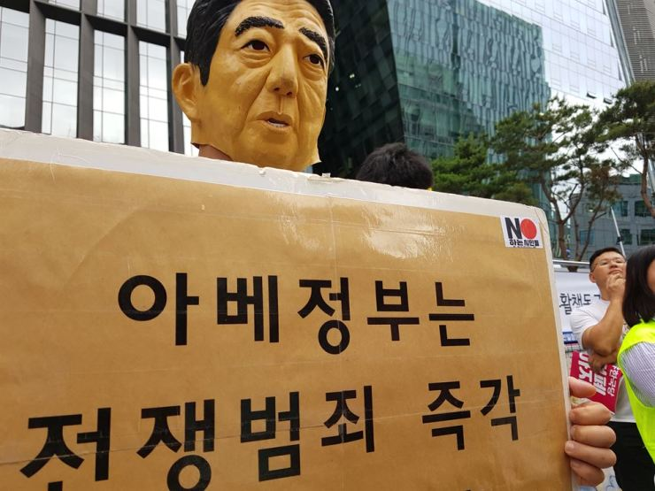 A masked protester dressed as Japanese Prime Minister Shinzo Abe holds a sign calling on the Abe administration to apologize for Japan's past war crimes, in front of the former site of the Japanese embassy site in downtown Seoul, Saturday. / Korea Times photo by Hong In-taek