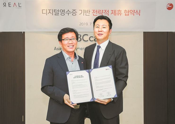 BC Card's Executive Vice President of Marketing Kim Jin-cheol, left, poses with The Real Marketing CEO Son Jong-hee, after the two signed an agreement on issuing digital receipts, at BC Card's headquarters in southern Seoul, Thursday. The initiative aims to reduce the use of paper receipts and protect the environment. / Courtesy of BC Card