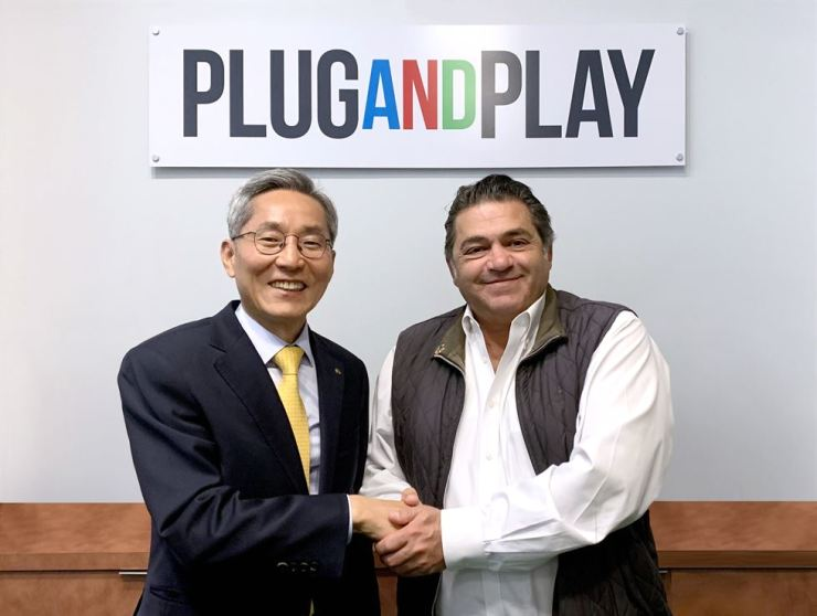 KB Financial Group Chairman Yoon Jong-kyoo, left, shakes hands with PLUG and PLAY CEO Saeed Amidi at the platform company's headquarters in Sunnyvale, California, April. / Courtesy of KB Financial Group
