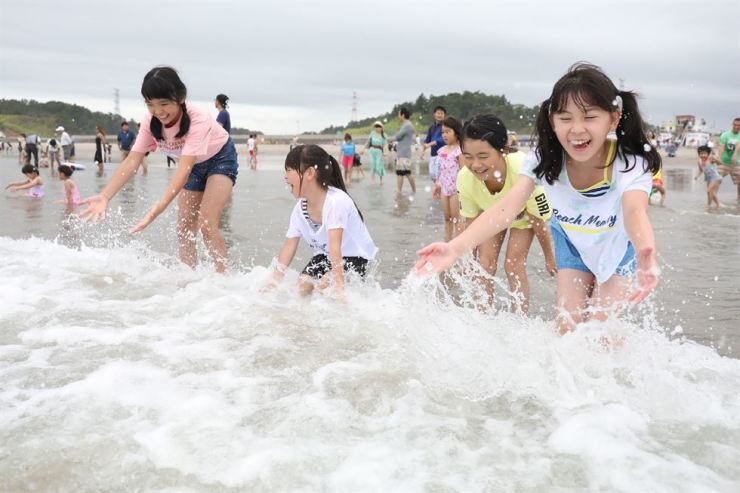 Children play with waves during the opening of the beach to members of the public at Kita Izumi in Minami Soma city, Fukushima Prefecture, July 20. The beach was closed for more than eight years following the Fukushima Daiichi nuclear power plant accident in 2011. AFP