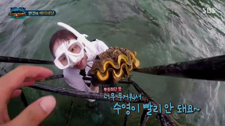 A scene from 'The Law of the Jungle,' aired on SBS, June 30, shows Lee Yeol-eum taking with her a giant clam from underwater at Hat Chao Mai National Park in Thailand in March 2019. Courtesy of SBS