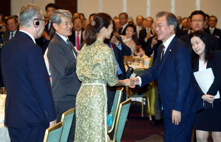 President Moon Jae-in, right, shakes hands with a participant at a meeting with Korean residents in Japan, Osaka, in this June 27 file photo. Korea Times file.