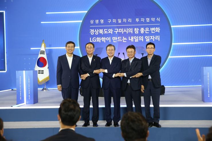 President Moon Jae-in and LG Chem Vice Chairman and CEO Shin Hak-cheol, left, hold hands with Gumi Mayor Jang Se-yong, second from left, and North Gyeongsang Province Governor Lee Cheol-woo, second from right, at the Gumico convention center in Gumi, North Gyeongsang Province, Thursday, during a signing ceremony for an investment to build a new battery factory in the town. / Courtesy of LG Chem