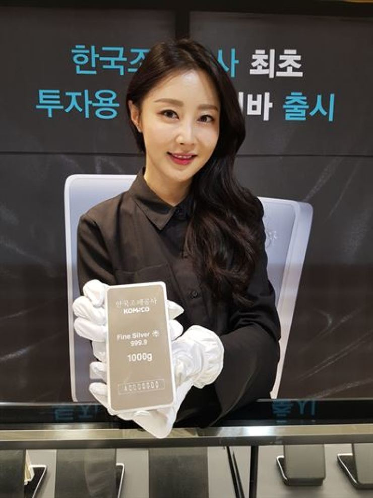 A model displays a 1 kilogram silver bar at Dansungsa Theater in Seoul in this April 23 file photo. The silver bar released May 2 by the Korea Minting, Security Printing & ID Card Operating Corp. (KOMSCO) is already sold out. / Courtesy of KOMSCO