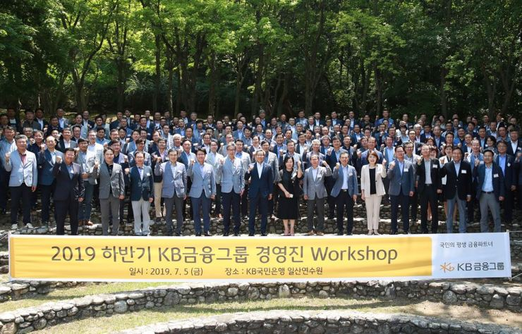 KB Financial Group Chairman Yoon Jong-kyoo, front row seventh from left, poses with executives of the group's affiliates at a management-level workshop, held at KB Kookmin Bank's training center in Ilsan, Friday. They shared cases of innovative services development and plans for the latter half of 2019. / Courtesy of KB Financial Group