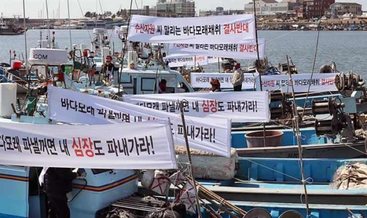 In this March 2017 photo, fishing boats carry banners protesting the sea sand harvest in waters off Gunsan, North Jeolla Province. Korea's sea sand harvest has been halted so far this year following fishermen's strong opposition, dealing a heavy blow to small and midsize ready-mixed concrete firms and builders. Yonhap