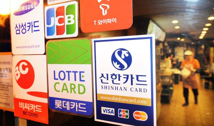 Stickers show credit cards that can be used at a restaurant in central Seoul in this file photo. Card firms are reducing the number of salespeople amid digitization and falling profit margin. Korea Times file