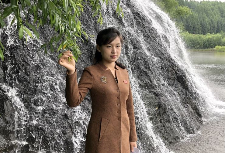 A woman poses for a photo by a waterfall atop Paektu Mountain, a volcano on the Chinese-North Korean border. TASS