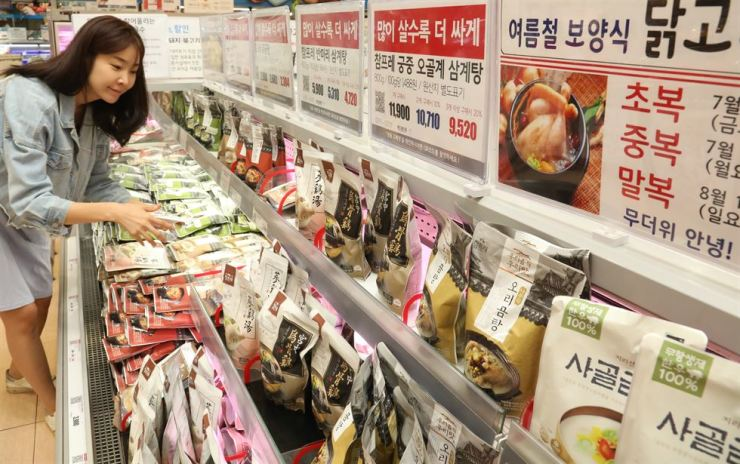 A consumer looks around a selection of health foods at a Lotte Mart store at Seoul Station, Thursday, on the eve of Chobok, the start of a long period of muggy weather that hits Korea between July and August. / Yonhap