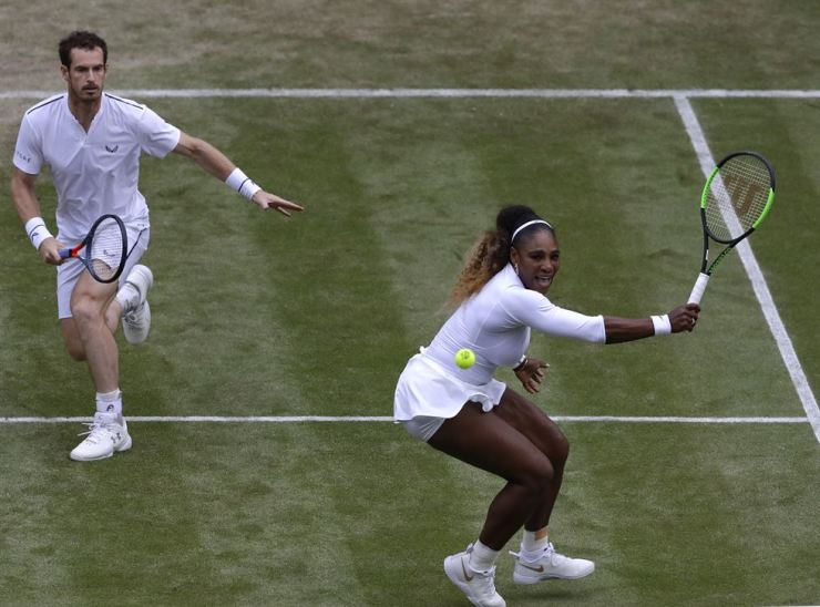 United States' Serena Williams returns the ball in a mixed doubles match with Britain's Andy Murray during day six of the Wimbledon Tennis Championships in London, Saturday. AP-Yonhap