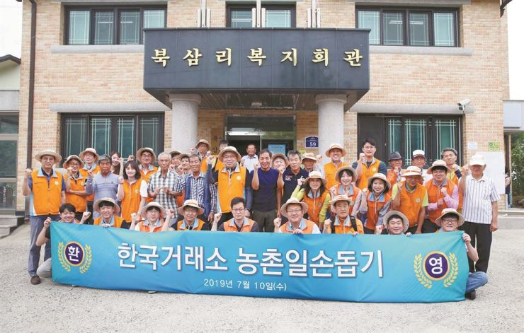 Korea Exchange (KRX) Management Support division head Chae Nam-ki, second row seventh from left, poses with the exchange's employees and farmers at Buksam Village in Yeoncheon County, Gyeonggi Province, Wednesday. Chae and 40 KRX workers volunteered at the village to help farmers there. / Courtesy of Korea Exchange