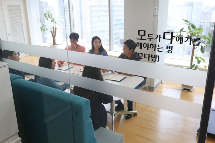 Employees of Woori Bank's digital division hold a meeting in a room labeled 'room where everyone has to say something.' This is a means to hear more from lower-level employees, who usually remain silent and listen to their superiors in Korea's hierarchical culture. / Courtesy of Woori Bank