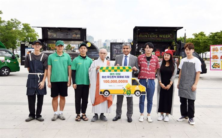 S-Oil CEO Hussain A. Al-Qahtani, fifth from left, poses with Work Together Foundation Chairman Song Wol-joo, fourth from left, and food truck entrepreneurs at Yeouido Hangang Park in Seoul, July 12. The refiner donated 100 million won ($84,912) to support the fuel costs of food truck entrepreneurs. / Courtesy of S-Oil