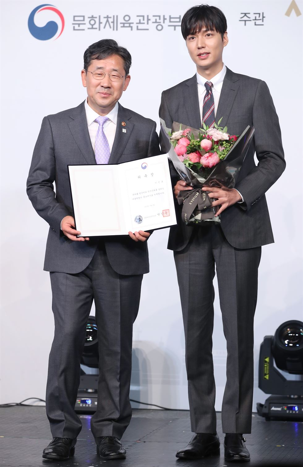 Actor Lee Min-ho, right, and Minister of Culture, Sports and Tourism Park Yang-woo hold a cardboard certificate appointing Lee as PR ambassador for the state-run King Sejong Institute at the Plaza Hotel in Seoul, Tuesday. The institute, under the ministry's control, offers Korean language and cultural education programs for foreigners interested in the country. As of June this year, the institute had 180 offices in 60 countries, teaching nearly 60,000 foreigners each year. Yonhap