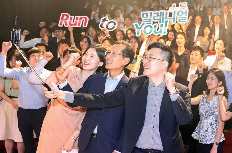 KEB Hana Bank CEO Ji Sung-kyoo, front row center, takes a selfie with bank employees at a theater in Daehangno, Seoul, Friday, after watching a play there. The event is part of the CEO's efforts to enhance communication with and better understand millennial generation employees. / Courtesy of KEB Hana Bank