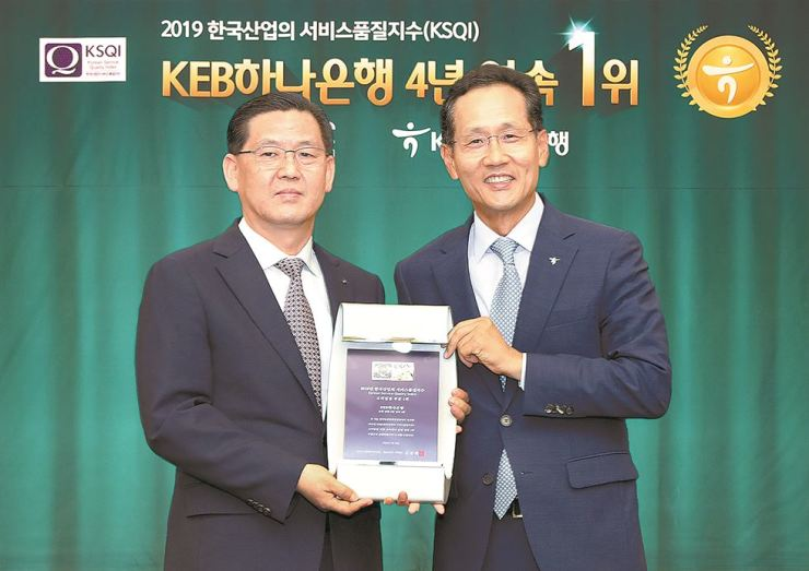 KEB Hana Bank CEO Ji Sung-kyoo, right, holds a plaque with Korea Management Association Consulting President and CEO Kim Jong-lib at the bank's head office in Seoul, Thursday. The bank has topped the customer service category in the consulting and rating agency's Korea Service Quality Index for four years in a row. / Courtesy of KEB Hana Bank