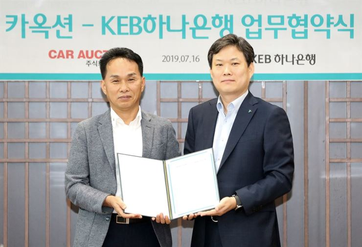 KEB Hana Bank sales division director Lee Jang-sung, right, holds an MOU with used car trading platform app Car Auction CEO Jang Young-soo at the bank's head branch in Seoul, Tuesday. / Courtesy of KEB Hana Bank