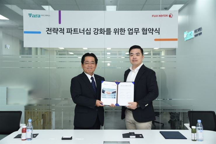 Fuji Xerox Korea President Takashi Otani, left, poses with Kang Ho-yeon, CEO of Tara Graphics, after the former agreed to provide printers to 18 branches of Tara Graphics, at the latter's headquarters in Seoul, Wednesday. / Courtesy of Fuji Xerox Korea
