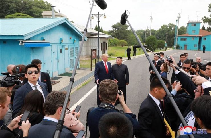 U.S. President Donald Trump and North Korean leader Kim Jong-un stand before a group of journalists at the Pamunjom truce village last Sunday. Yonhap