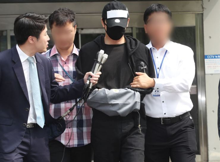 Actor Kang Ji-hwan, handcuffed, is escorted out of the Bundang Police Station after questioning on Thursday. Yonhap