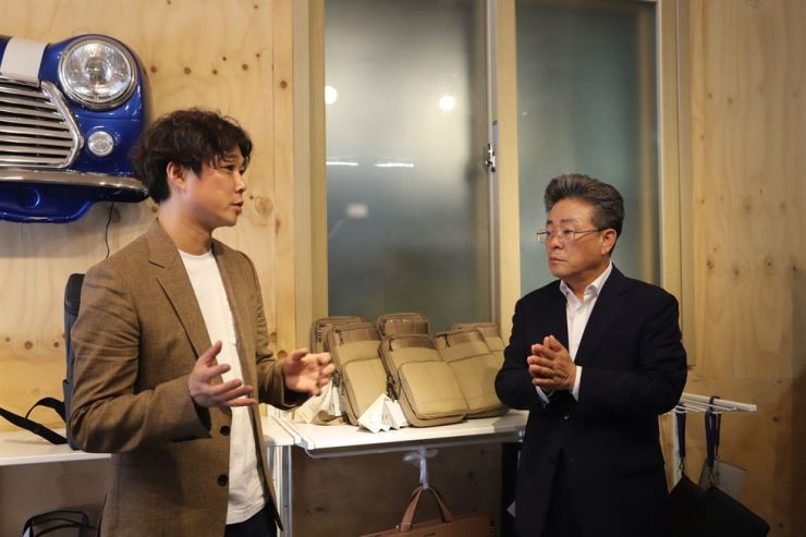 Morethan CEO Choi Yi-hyun, left, speaks to Ulleung County Governor Kim Byeong-su during a branch opening ceremony on the island, Friday. Courtesy of SK Innovation