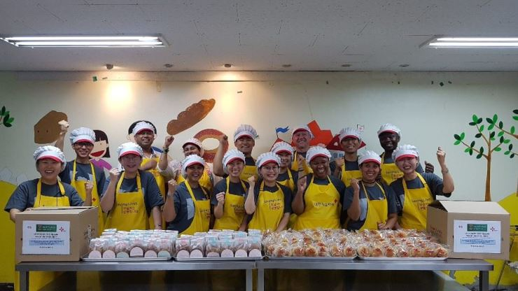 Charge d'Affaires Gert du Preez, back row third from left, of the South African Embassy in Korea, and other participants pose during their visit to the Korea Red Cross Joongang Voluntary Service Center in Jongno-gu, central Seoul, Thursday. The embassy staff baked bread and shared it with the needy in commemoration of Nelson Mandela International Day. The United Nations has celebrated every July 18 as Nelson Mandela International Day in honor of the late South African president and the values he embraced, including democracy, freedom, equality, diversity, reconciliation and respect. / Embassy of South Africa