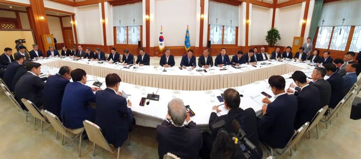 President Moon Jae-in and dozens of business leaders hold a meeting at Cheong Wa Dae to discuss how to deal with Japan's export restrictions, Thursday. / Yonhap