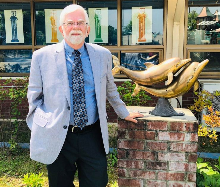 John Blom stands next to a dolphin statue in front of Seoul American Elementary School, where he used to be principal. / Courtesy of Yongsan Legacy