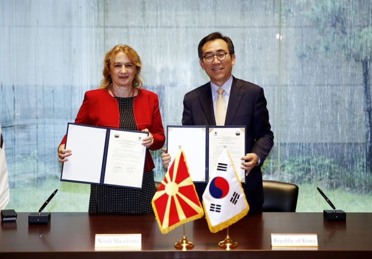 Korean Ambassador to the U.N. Cho Tae-yul, right, and North Macedonian Charge d'Affaires at the U.N. Sanja Zografska Krsteska pose after signing a joint diplomatic treaty at U.N. headquarters in New York City, Thursday. / Yonhap