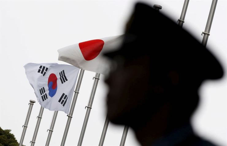 A police officer stands guard near Japanese and South Korean national flags at a hotel, where the South Korean embassy in Japan is holding a reception to mark the 50th anniversary of the normalization of ties between Seoul and Tokyo, in Tokyo, June 22, 2015. Reuters-Yonhap