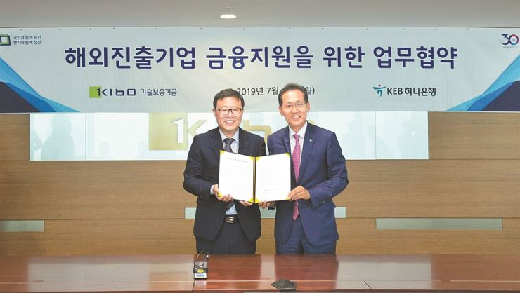 KEB Hana Bank CEO Ji Sung-kyoo, right, poses with Korea Technology Finance Corp. (KOTEC) Chairman Jeong Yoon-mo after the two signed an agreement on supporting small- and medium-sized enterprises (SMEs), at KOTEC's office on Yeouido, Seoul, Monday. KEB Hana Bank will provide loans for SMEs' overseas affiliates. / Courtesy of KEB Hana Bank