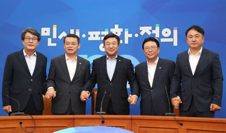 Secretaries-general of five political parties hold hands at the National Assembly, Tuesday, after agreeing to a meeting between leaders of the parties and President Moon Jae-in on Thursday to tackle Japan's trade restrictions on South Korea. From left are Reps. Kim Kwang-soo of the minor opposition Party for Democracy and Peace; Lim Jae-hun of the minor opposition Bareunmirae Party; Yun Ho-jung of the ruling Democratic Party of Korea; Park Maeng-woo of the main opposition Liberty Korea Party; and Shin Jang-sik of the Justice Party. Yonhap
