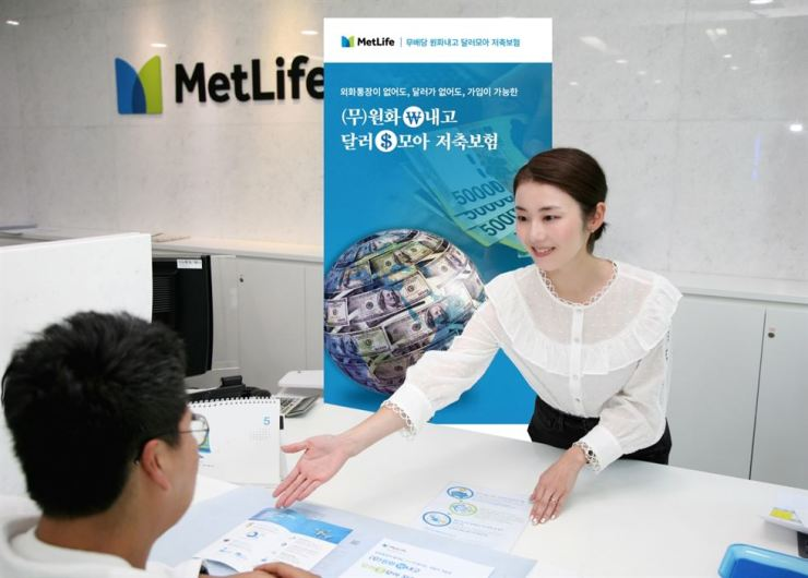 A MetLife Korea employee introduces a product that takes premiums in Korean won and pays claims in dollars to a customer in this file photo. / Courtesy of MetLife Korea