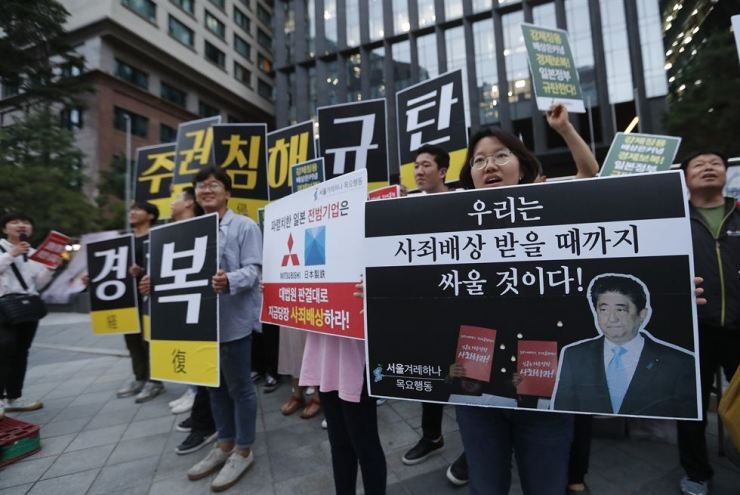 College students stage a rally denouncing the Japanese government's decision on their exports to Korea in front of the Japanese Embassy in Seoul, Thursday. AP