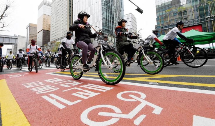 Citizens cycle along a color-coded bike path and street as part of a car-free parade in Jongno, Seoul, in this April 2018 photo. Korea Times file