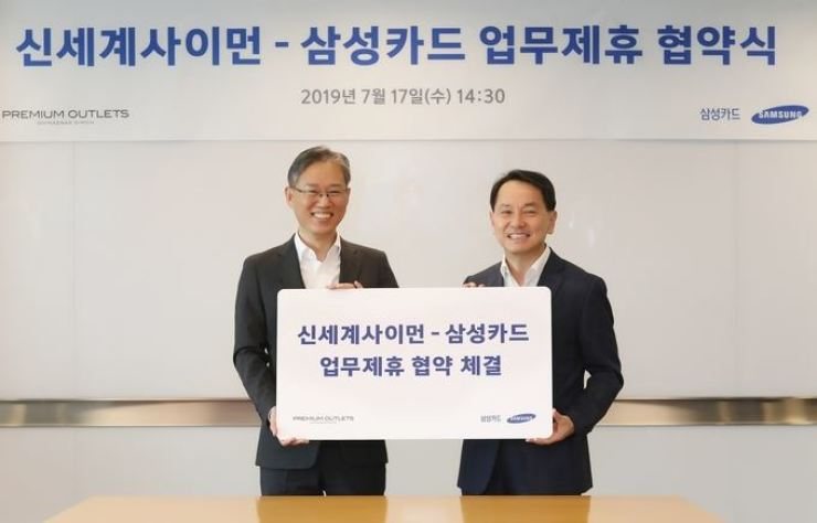 Samsung Card CEO Won Ki-chan, right, poses with Shinsegae Simon CEO Cho Chang-hyun after signing a business alliance at the card firm's head office in central Seoul, Wednesday. / Courtesy of Samsung Card