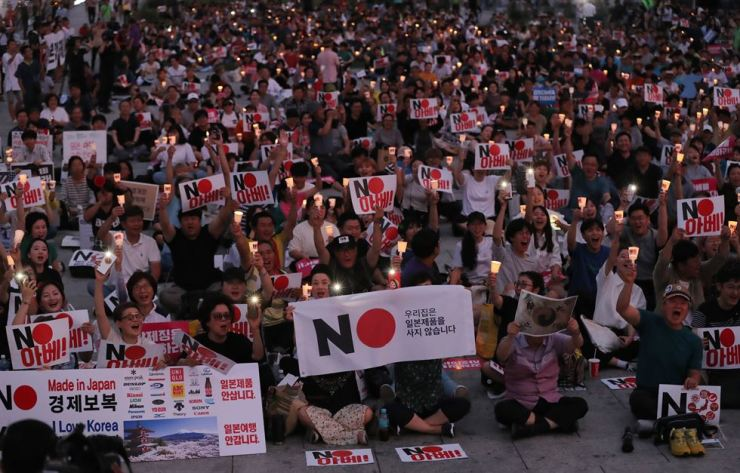 Citizens and activists participate in a candlelight vigil in central Seoul, Saturday, to protest Japan's export curbs on Korea. / Yonhap