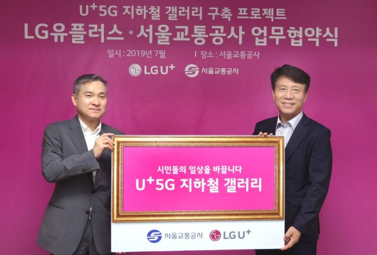 Ha Hyun-hwoi, left, vice chairman and CEO of LG Uplus, poses with Seoul Metro CEO Kim Tae-ho after agreeing to launch an AR technology-based art gallery at a subway station in Seoul, at the latter's office in Seongdong-gu, Seoul, in this photo provided by the mobile carrier Sunday. / Courtesy of LG Uplus