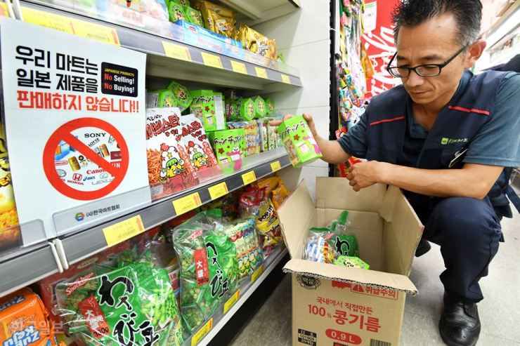 Next to a sign that reads 'We do not sell Japanese goods,' an employee removes Japanese snacks from the shelves at a supermarket in Seoul, July 8. Korea Times file